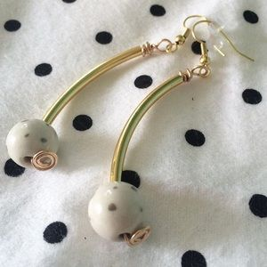 Cute curved gold earrings with porcelain bead